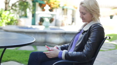 A Young Woman Checks Text Messages at Outdoor Cafe Stock Footage
