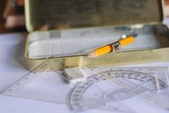 Compasses, pencil and rulers on squared paper Stock Photos