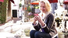 A Young Woman Smiles Receiving a Text Message Outdoors Near a Fountain Stock Footage