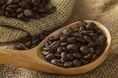 Coffee beans on burlap sack and spoon - stock photo