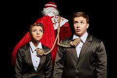 Tense business people tied to Santa Claus Stock Photos