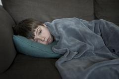Boy with flu, lying on the sofa Kuvituskuvat