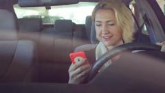 A Young Woman Checks Text Messages on Cell Phone While Driving Stock Footage