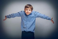 teenager boy of 10 years European appearance spread his hands - stock photo