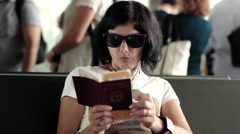 Woman checking her passport and fly tickets while waiting in the airport Stock Footage