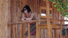 Woman is relaxing in a windy day of summer leaning against a railing of wood Stock Footage
