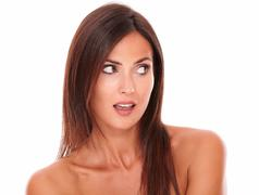 head and shoulders portrait of surprised attractive female looking to her lef - stock photo