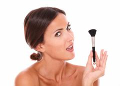 Stylized portrait of beautiful young woman with make up brush for pampering h Stock Photos