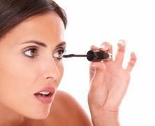 close up portrait of hispanic female pampering her eyelash with mascara with  - stock photo