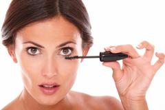 Close up portrait of afraid woman with brown eyes applying mascara with nude  Stock Photos
