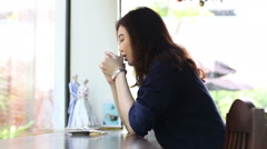 Beautiful happy asian women with mug in hands at coffee shop. - stock footage