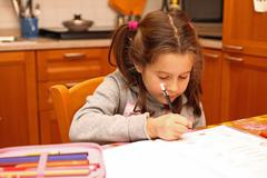 beautiful little girl writes with pencil on book school exercises - stock photo