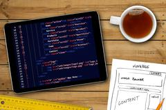 Website wireframe sketch and programming code on digital tablet screen Stock Photos