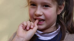 Little girl with the tooth that dangles by her hand Stock Footage
