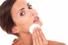 Stylized portrait of sensual and pretty woman pampering her face with cotton  Stock Photos