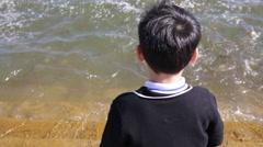 Asian child give alms food for fish around the river Stock Footage