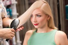 Hairstylist makes hairstyle for beautiful girl Stock Photos