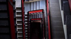 Upward rising shot of black and red stairwell and staircase Stock Footage
