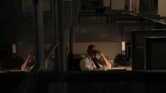 Relaxed business man working late at the office in cubicle Stock Footage