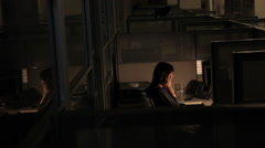 Business woman in a cubicle alone at her computer working late in the office Stock Footage