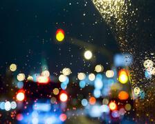 Raindrops on windshield car. blurred big city lights Stock Photos