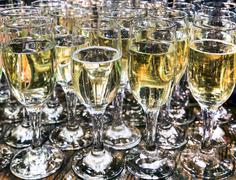 Row of glasses filled with champagne lined up ready to be served Stock Photos