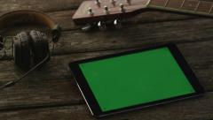 Tablet PC with Green Screen Laying on Wooden Table next to Guitar and Headphones Stock Footage