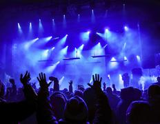 Silhouettes of people and musicians in big concert stage. bright beautiful ra Stock Photos