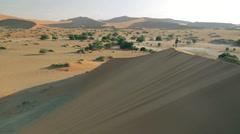 Man walks in aerial on top of dune in desert of Sossusvlei, Namibia, Slow Motion Stock Footage