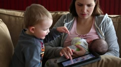 A mother nursing her baby while on ipad and toddler plays Stock Footage