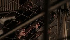 Three kidnapped children attempting to come out through barred door. Stock Footage