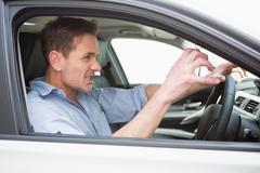 Handsome man experiencing road rage - stock photo