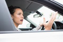Pretty businesswoman experiencing road rage - stock photo