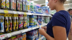 Young Woman with Choosing Tooth Brush in a Shop. Stock Footage