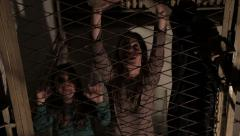 Human trafficking, trapped children trying to get out behind bars, symbolic shot Stock Footage