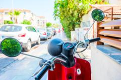 Red motorcycle stands on the sidewalk on the street Stock Photos