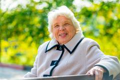 portrait of happy pensioner sitting on a bench in the park - stock photo