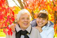 laughing grandmother and granddaughter in the park with beautiful red leaves - stock photo