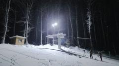 Ski elevator and people skiing at night - stock footage