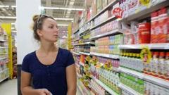 Woman in a Supermarket Choosing Bottle of Juice Stock Footage