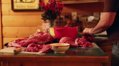 A hunter cuts up elk meat on his kitchen counter Stock Footage