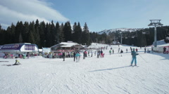Panoramic view of people skiing on mountain slope, pan right. Stock Footage