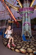 Child rides a carousel in the evening park. Stock Photos