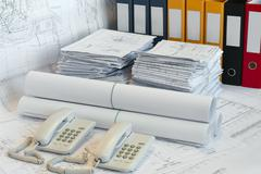 big heaps of design and project drawings, folder and two telephoes on the tab - stock photo