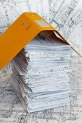 big heap of design and project drawings under yellow folder on the table surf - stock photo