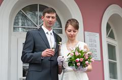 bride and groom are near registry office with glasses of champagne - stock photo