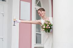 woman a bride with glass of wine near a registry office buildings. table is h - stock photo