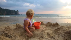 Girl in purple swimsuit play in the sand Stock Footage