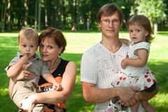 Happy family of four people. two adult parents and two children Stock Photos