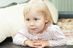 Little child a dlond girl sitting on sofa and looking through Stock Photos
